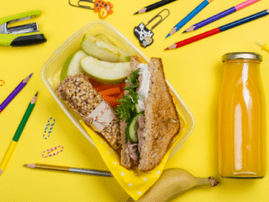 yellow background filled with colored pencils, a lunch box with a sandwich and a glass bottle of juice