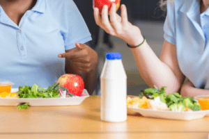 Photo of child holding an apple at cafeteria table with lunch tray. Plastic un-labeled milk bottle in front.