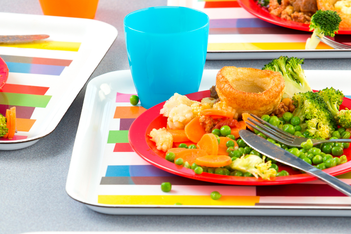 Cafeteria table with children's meal trays with plated food