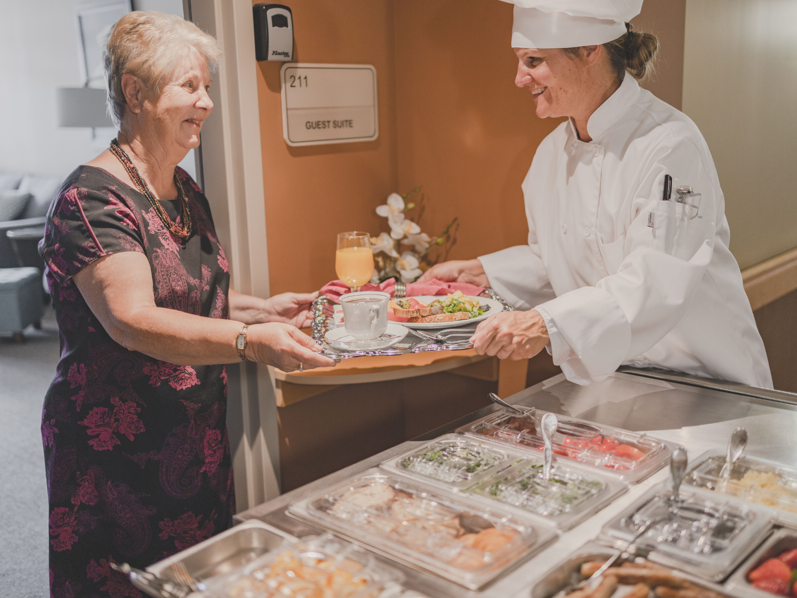 Chef serving senior care resident in their room and handing meal tray