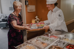 Chef with SuzyQ meal cart in senior care community hallway serving resident