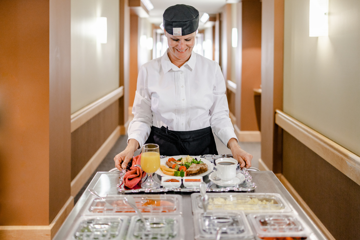 Chef with mobile food cart in hallway