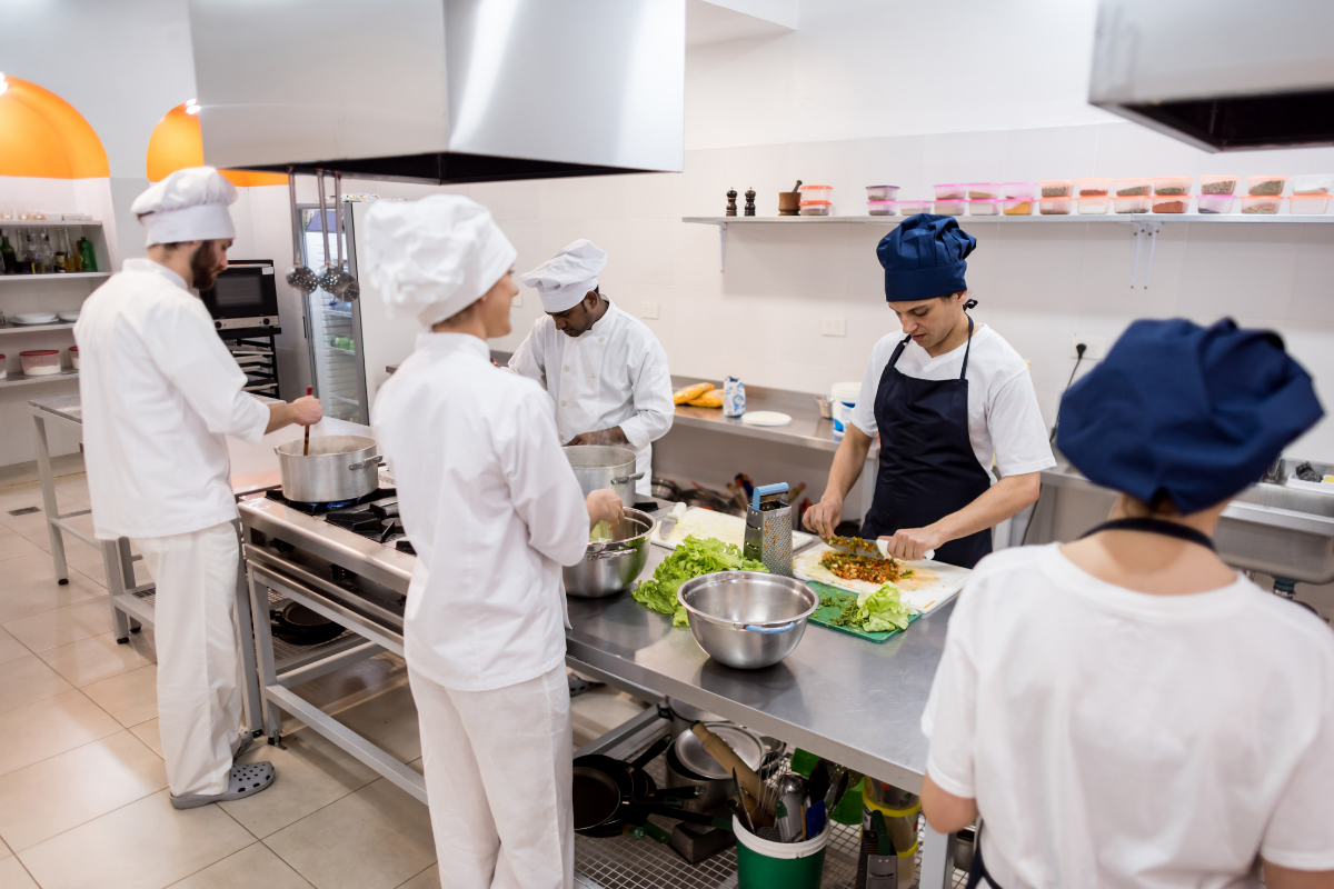 Commercial Kitchen with Chefs Standing Around a Prep Table